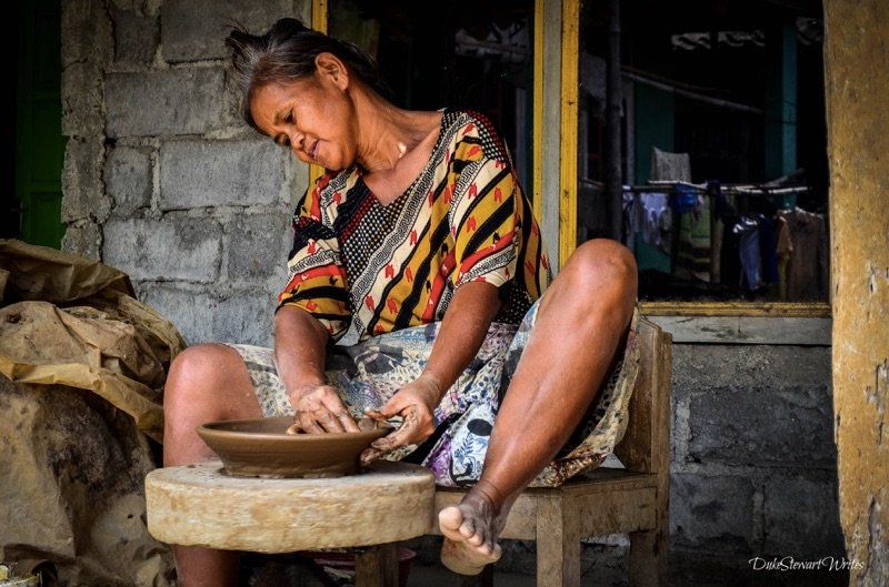 A woman making clay bowls in Indonesia